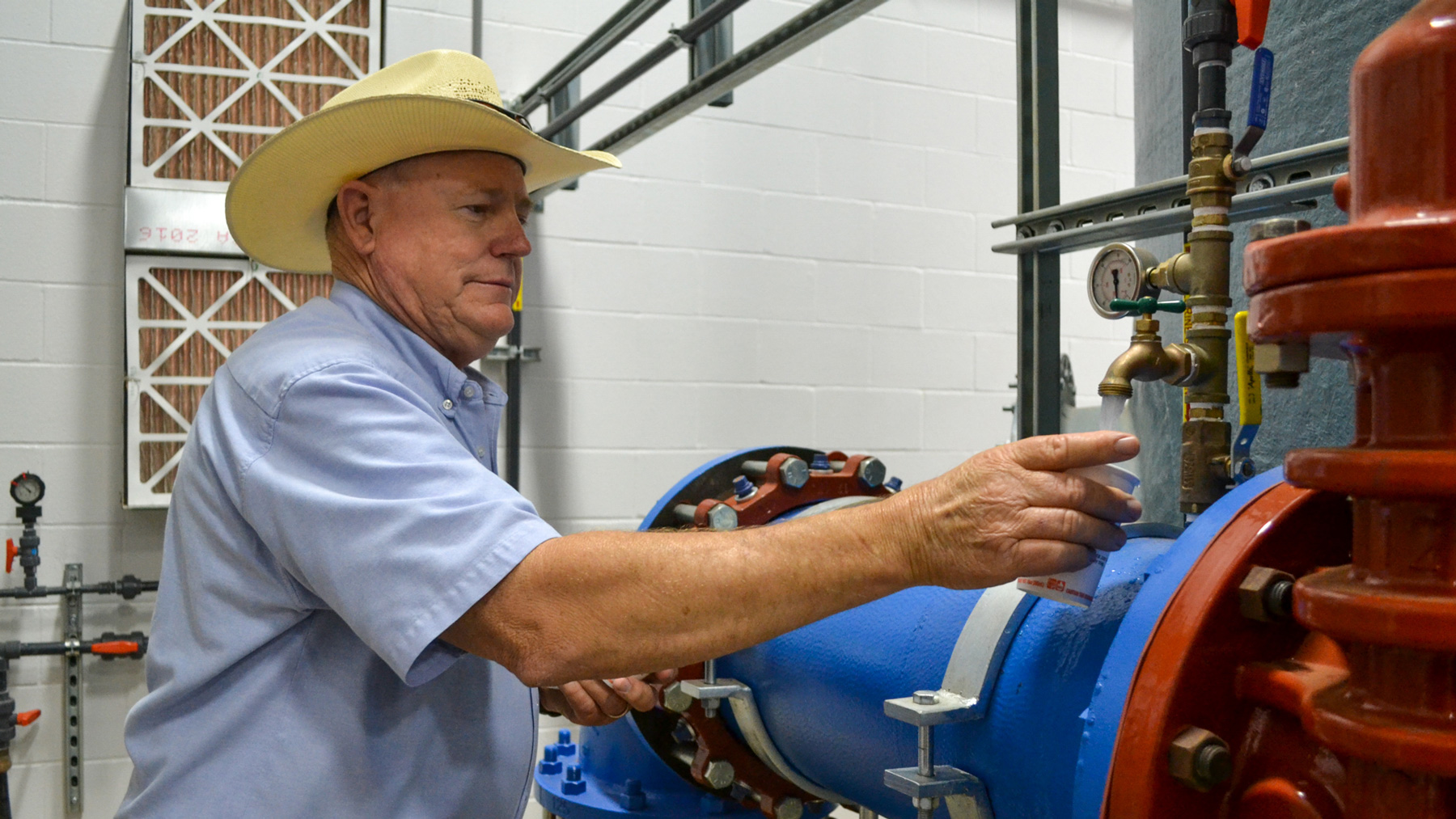 "Public Works Director Doug Hutcheson fills a cup with water at the water treatment plant in Wolfforth, Texas. ""We've tried to comply. We're team players. We're wanting to fix it and get it on down the road,"" he said. (Elizabeth Sims/News21)"
